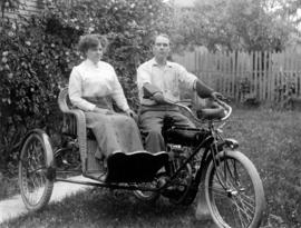 [Alfred T. Layne and Daisy D'Avara on earlier model motorcycle with sidecar]