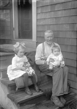 [Man sitting on steps with a baby and young girl with kitten sitting beside him]
