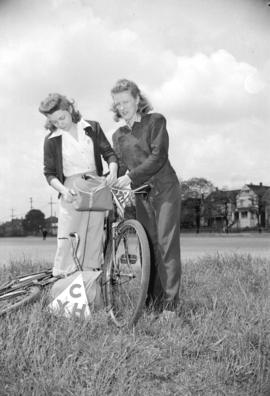 [Two women with bicycles in a field, taken for Canadian Youth Hostels]