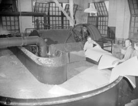 [Men adding sheets of material to a large vat of paper pulp at Westminster Paper]
