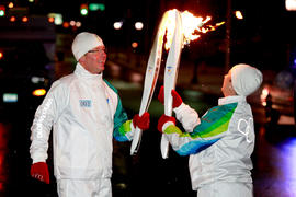 Day 60 Torchbearer 3 Nathan Majury passes the flame to Torchbearer 4 Mary Beth Reynolds in Kitche...