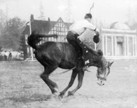 Rider on a bucking horse with false-front buildings in rear