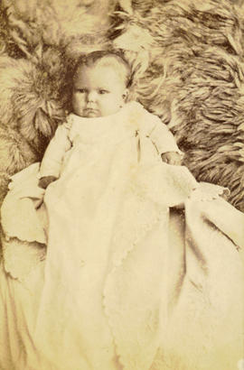 [Studio portrait of baby in christening gown on a fur blanket]