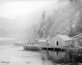 [Boat, logs, and buildings at small dock at site of Buntzen Lake Power Plant number one]