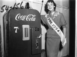 Nancy Hansen, Miss P.N.E., posing with Coca-Cola vending machine