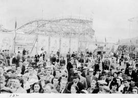 Crowd in front of sideshows and Baby Dipper rollercoaster attractions in midway carnival