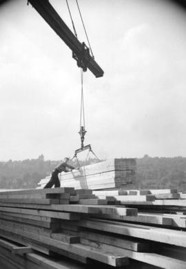 [Man positioning load of lumber being moved by crane]