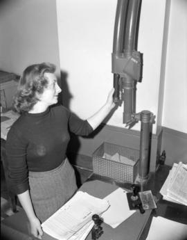 [Woman using the pneumatic tube system at the offices of Kelly Douglas Ltd.]