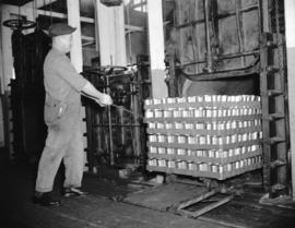 [A worker moving a pallet of cans] into an oven
