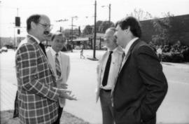Mike Harcourt speaking with three unidentified men