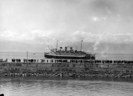 "[People line a breakwater to watch the S.S. ""Prince Robert"" leaving Victoria after the ..."