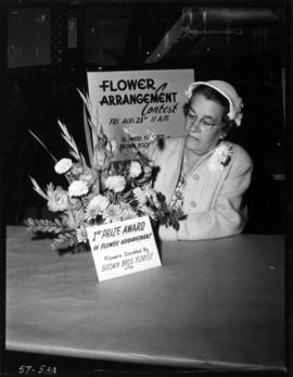 Woman with award-winning entry in flower arrangement contest in 1957 P.N.E. Home Arts show