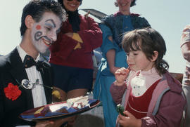 Man with painted face serving cake to child at Vancouver's 99th birthday celebration