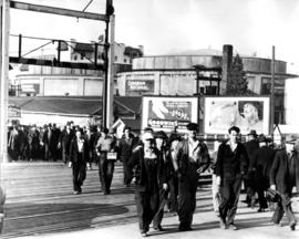 Group of workers walking, carrying metal lunchboxes