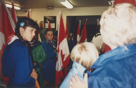 Girl Guides holding flags indoors during Canada Day Festival