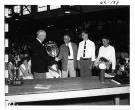 P.N.E. Past President J.S.C. Moffitt presenting trophy at awards ceremony for 1956 P.N.E. 4-H and...