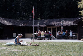 Seniors sitting on picnic benches outside of Camp Capilano with Totem Poles and Canadian flag