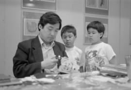 Man and two boys working on an arts and crafts project