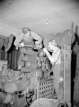 [Men in military uniforms fixing machinery in a machine shop]