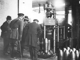 King George inspects a hydraulic press in a munitions factory