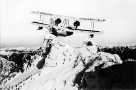 [Aerial view of biplane over The Lions]