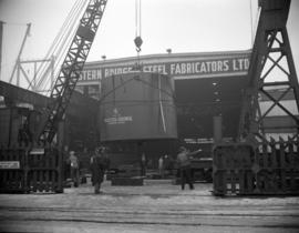[Men using a crane to move a large metal cylinder out of the Western Bridge and Steel Fabricators...
