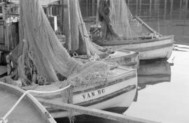 [Fishing nets draped over boats at dock]