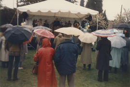 Crowd with umbrellas gathered around stage at dedication of Volunteer Park