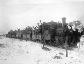 [Soldiers travel by train through a captured area on their way to the Western Front]