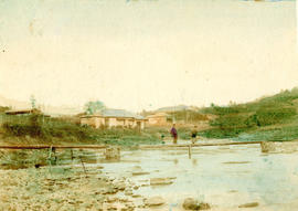 [View of people on bridge over river with buildings in background]