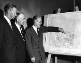 P.N.E. President J.F. Brown and others looking at proposed coliseum on map of P.N.E. grounds