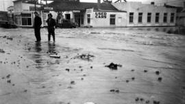 Two men in flooded street in front of Mac's Motors