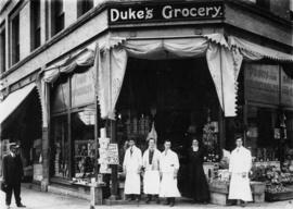 Duke's Grocery staff posing in front of store at the comer of Gore Avenue and Hastings Street