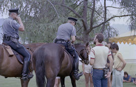Police officers on horseback talking to [Centennial employees]