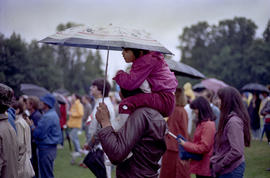 Girl sitting on man's shoulders under umbrella at Canada Day celebration