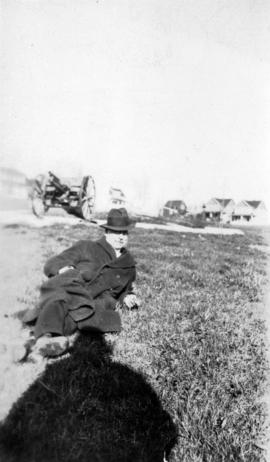[L.D. Taylor reclining on grass, with a cannon in the background]