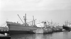 M.S. Stamitios C. Embiricos [at dock, with lumber-filled barges alongside]