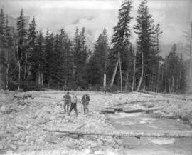 [Three men beside a creek  in Garibaldi District]