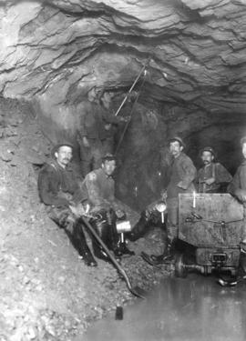 "Lake Buntzen tunnel enlargement [showing] ""mucking crew"" boring sown rock from roof of ..."