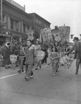[Chinese women and children bright costumes marching in the VJ day celebration parade in Chinatown]