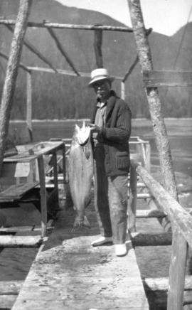 [L.D. Taylor holding freshly caught salmon at Stuart Island, B.C.]