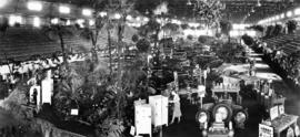 [Interior panorama of auto show at P.N.E. with Brown Bros.' palms, hanging baskets and sprin...