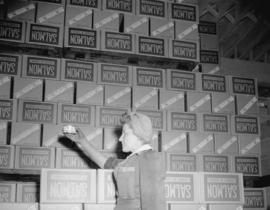 [Woman with canned salmon at] Imperial Canning