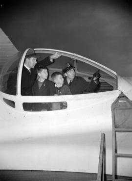[Man and boys with a pilot in the cockpit of a war plane manufactured by Boeing]