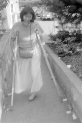 An unidentified young woman walking with the aid of crutches