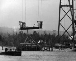 Long distance lens picture of first section of Bridge roadway.  Steel being raised from scow to c...