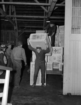 [Navy men loading crates of Red Cross supplies from a warehouse onto ship]