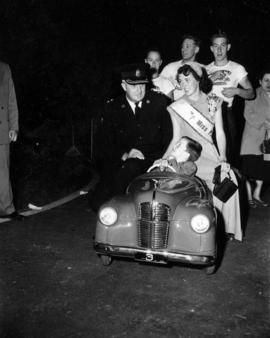 Miss P.N.E., police officer, and young boy with Austin pedal car