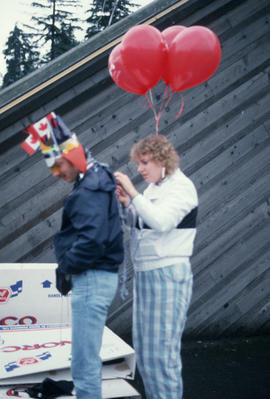 Woman and man with balloons at the Centennial Commission's Canada Day celebrations