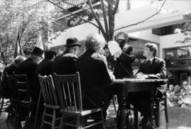 Group of actors at table during re-enactment